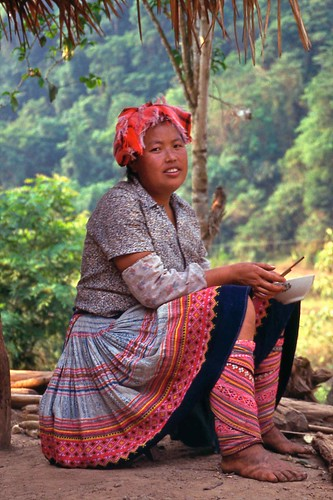 Flower Hani woman eating on her porch; Road from Mengla to Mohan, Xishuangbanna Region, Yunnan, China   by Lon&Queta