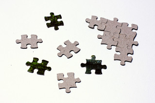 Scattered puzzle pieces next to solved fragment | by Horia Varlan
