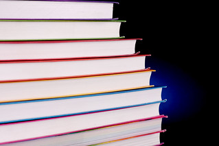Stack of colorful books with blue light behind them | by Horia Varlan