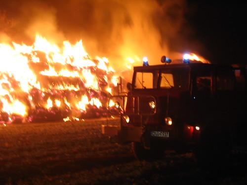 Samochód straży pożarnej i płonący stóg