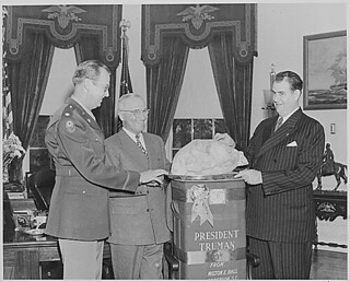 Photograph of Sen. Olin Johnston of South Carolina presenting President Truman with a turkey from Wilton E. Hall of Anderson, South Carolina, as Colonel Lewis Jackson looks on, 11/25/1946