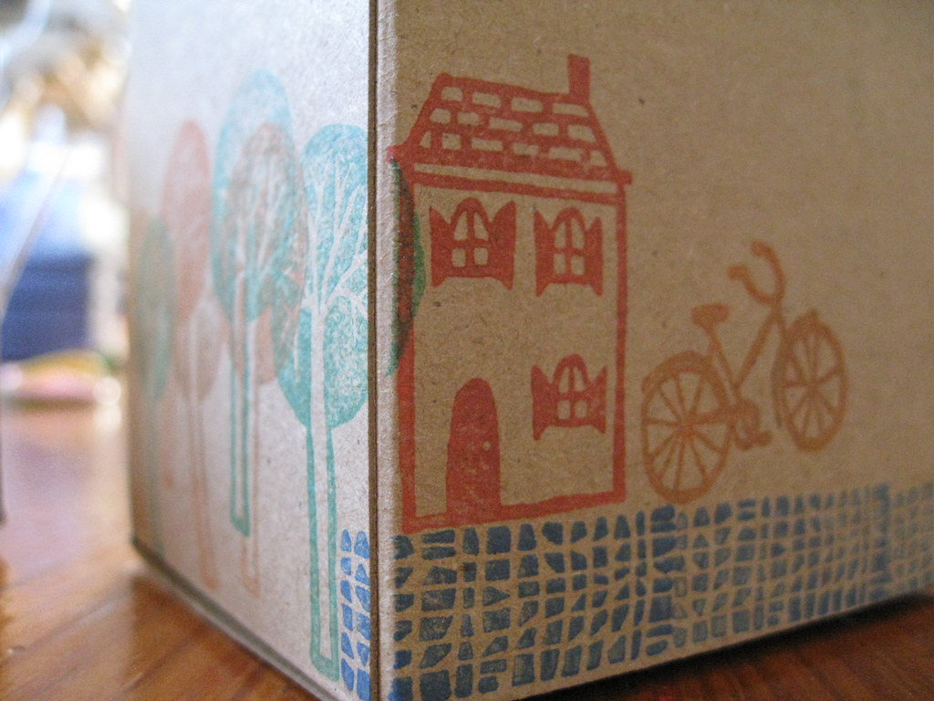 A moving box with a drawing of a house and trees on it