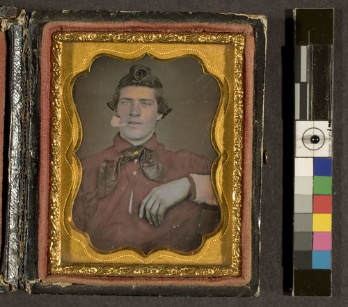 Portrait of young man in red shirt, smoking a clay pipe | by George Eastman Museum