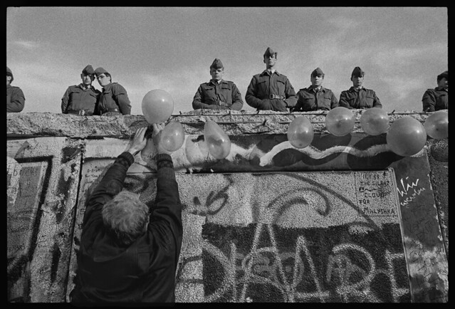 """A West German man places balloons on the wall as East German """"Vopos,"""" or Volkspolizei, watch from atop it near the Brandenburg Gate in Berlin, West Germany on Nov. 4, 1989, by James Nachtwey"""