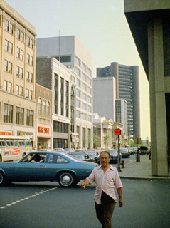 Some guy truckin' down the streets of New Haven, Connecticut with a blue 1973 Chevy Nova behind him. Aug 1974   by wavz13