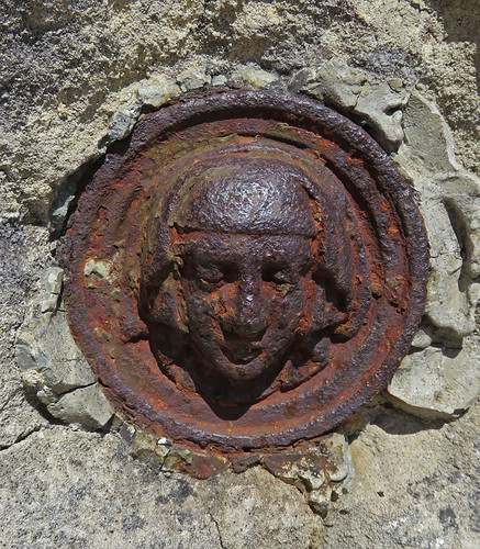 A rusty medallion embedded in the wall surrounding the chapel at Cap Fagnet on the Normandy Coast of France