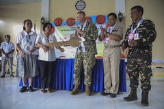 U.S. Navy Capt. James Meyer, commodore of Pacific Partnership's Task Force Forager, passes the key to Caba National High School to Josefina Samy during a ribbon cutting ceremony.(U.S. Marine Corps/Sgt. James Gulliver)
