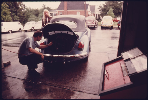 Service Station Mechanic Adjusts the Engine for a Young Woman Whose Vehicle Had Failed the Emissions Test at an Auto Emission Inspection Station in Downtown Cincinnati, Ohio...09/1975 | by The U.S. National Archives