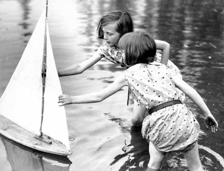 Two young girls reaching for a toy sailboat, Seattle, Washington