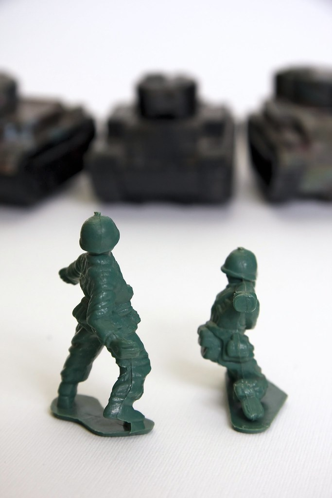 Green toy soldiers fighting black tanks | Two green toy sold