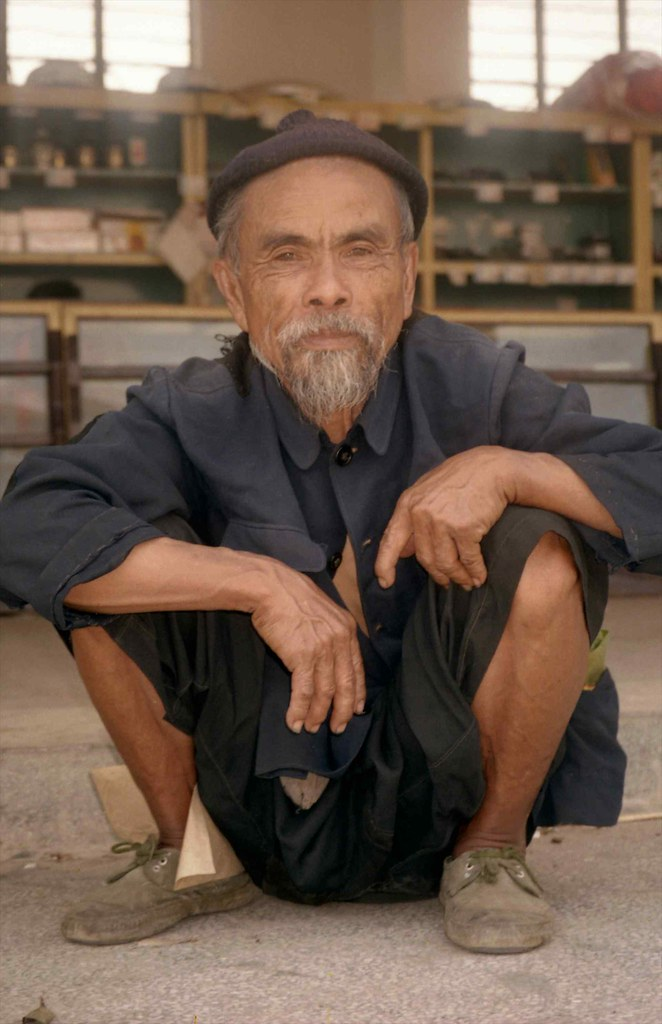 Old man squatting on steps; Market at Menghum, Xishuangbanna, Yunnan, China