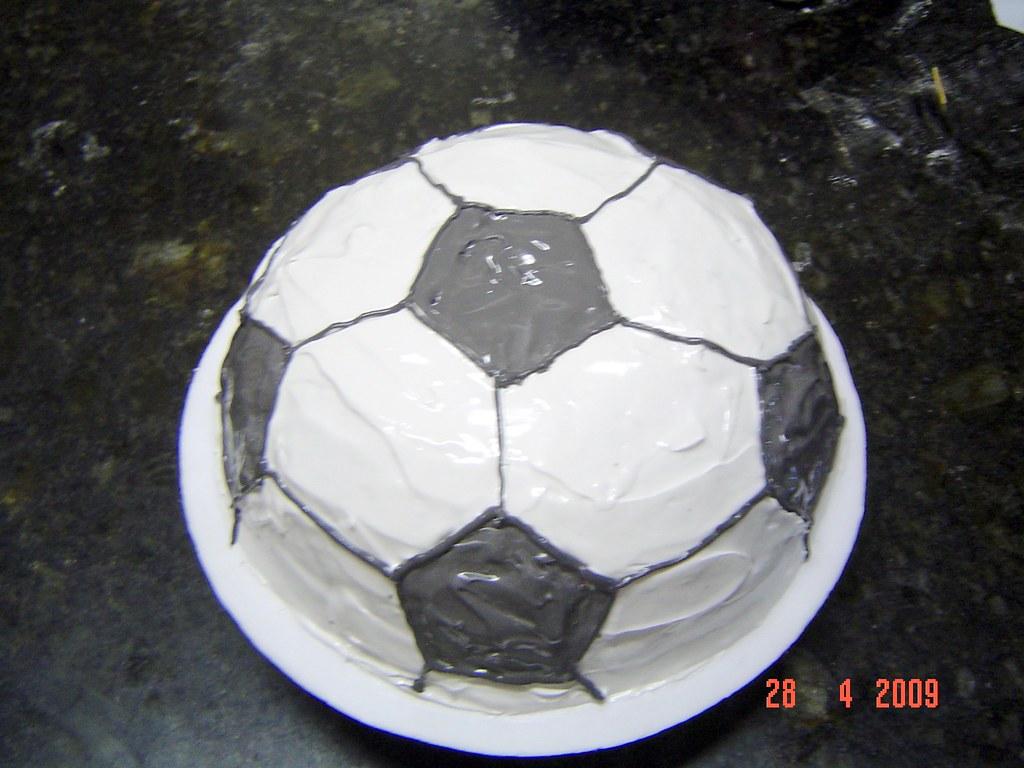 ff18a838b by Fa Bolo de chocolate coberto com glacê em formato de bola de futebol.