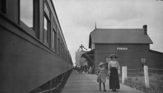 People walking along platform at train station in Ponoka, Alberta / Gens marchant le long du quai à la gare de Ponoka (Alberta)