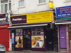 """A small terraced shopfront with large photo adverts for beer, snacks, and breakfast items covering the windows.  A yellow and purple sign above reads """"Premier Express / Ellalan Convenience Store / 6am to 11pm / 7 days a week""""."""