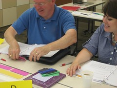 At the Summer Institute, teachers work the problems in each other's lessons and provide feedback for the revised versions. These teachers are using paper manipulative to see how fourth graders might approach the question,