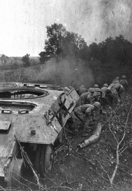Soviet soldiers take cover with destroyed german tanks