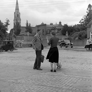 Man talking to woman in cobbled square, church visible in background, Co. Dublin