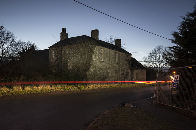 Light trails in front of derelict house