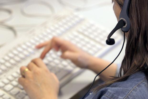 Una teleoperadora atiende la llamada de un consumidor en el teléfono de atención al cliente