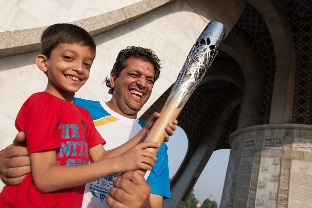 Father and son hold the Queen's baton at the Minar-e-Pakis… | Flickr