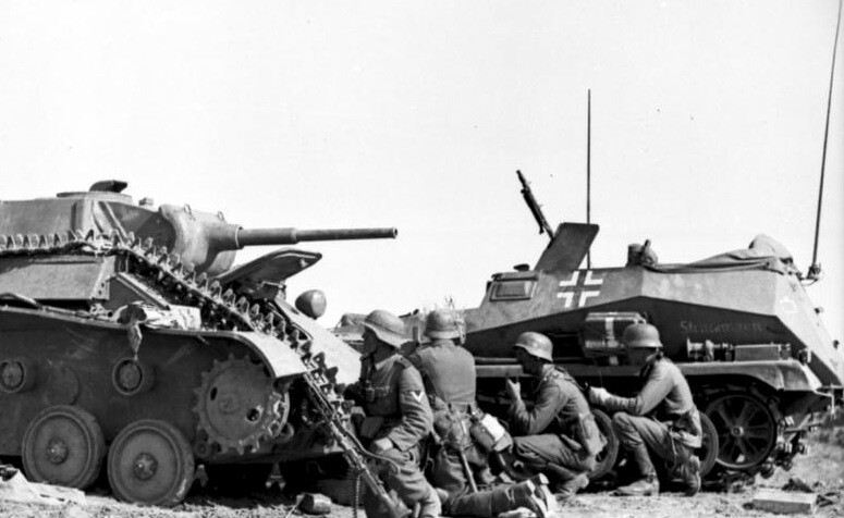 German troops take cover behind a knocked out T-70 light tank