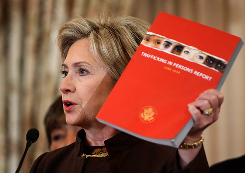 Hillary Clinton holds up the Trafficking in Persons Report 2009