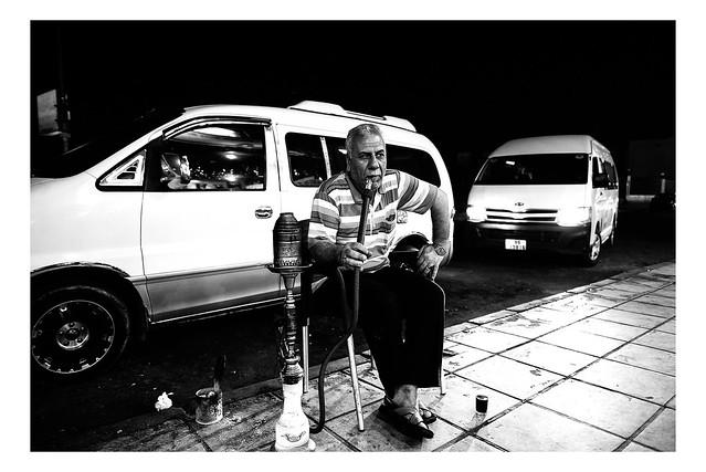 A man smokes shisha outside in Aqaba, Jordan
