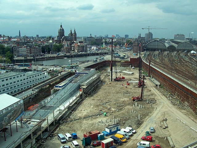2007.08 - 'City is building...' - Amsterdam photos and pictures, a cityscape with excavations and construction sites at the Oosterdok- train tracks and Central station to the right; Dutch city + geotag, Arjan Heijnsbroek, The Netherlands