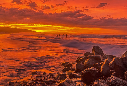 dunedin new zealand clair beach ocean waves sunrise dawn photo image picture photos images pictures reflection red rocks surf fire sky oceanview world flame flaming seascape otago