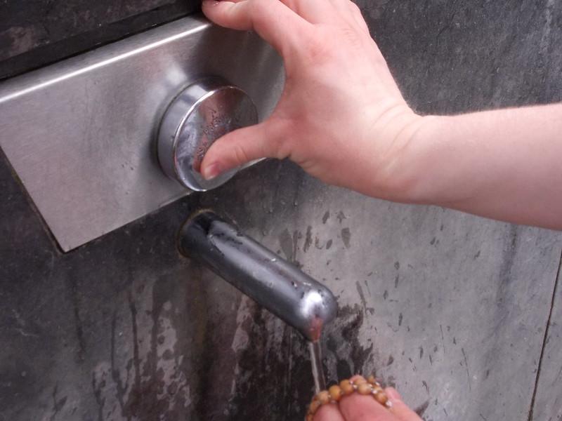 Pilgrim washing Rosary Beads