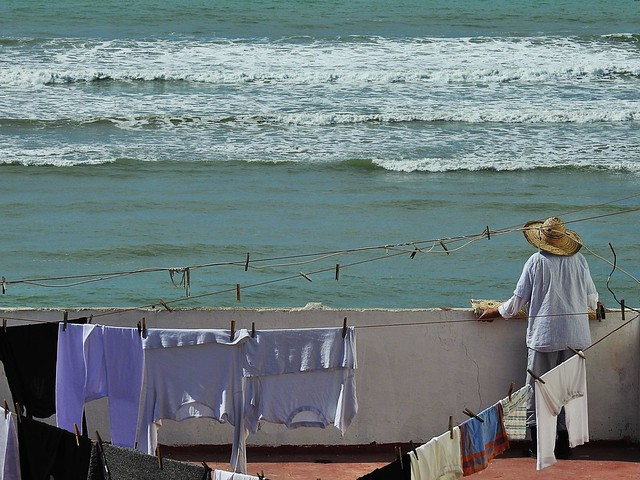 From a medina´s house, man contemplating the ocean & the sunset. Assilah / Morocco.