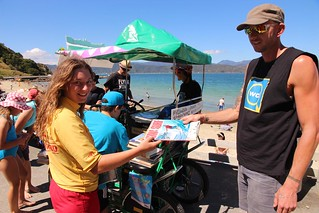 Simon of the Wellington City Library Book Bike offers some appropriate reading for a Scorching Bay lifeguard