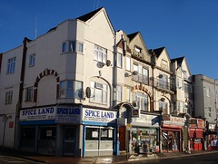 The end of a terrace of three-storey buildings with shops on the ground floor.  Satellite dishes festoon the upper floors.  The first-floor windows are surrounded by arches, and the roofs have pointed gable ends.
