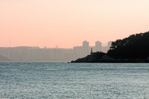 ocean sunset sea lighthouse building silhouette skyline skyscraper haze cityscape wind windy shore busan highrise cape southkorea seaofjapan haeundaebeach oryukdo canon40d dongbaekseomisland