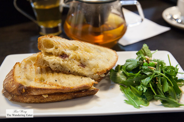Grilled cheese sandwich on sourdough bread with mixed salad with herbs and fresh peas