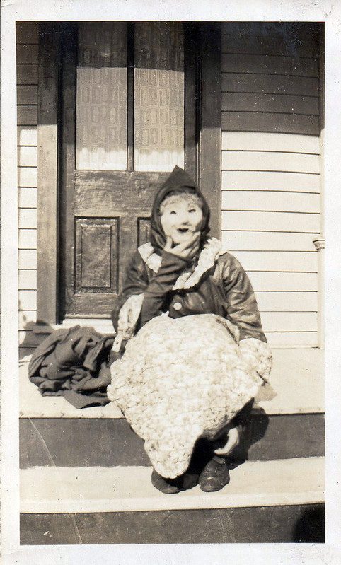 Woman in Halloween mask sits on a porch