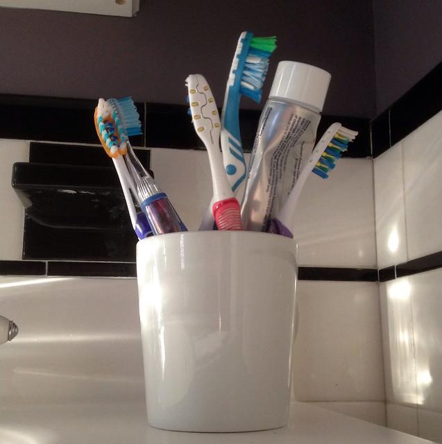 pot avec brosses à dents et dentifrice dans une salle de bains