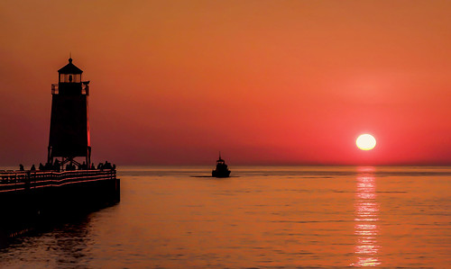 sun sunset sundown dusk evening lake michigan sea seascape lighthouse pier golden water waters boat summer warm night railing glow reflection sky skies horizon beach silhouettes people