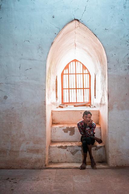 Stock shot of Asian man sitting under church window