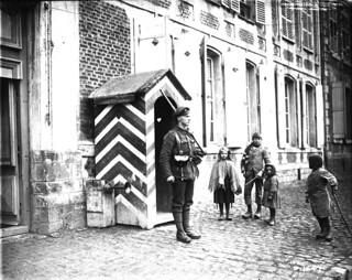 """Children of a newly captured village are very curious about this """"British Tommy"""" on sentry duty, May 1917 / Une sentinelle britannique pique la curiosité des enfants dans un village nouvellement conquis, mai 1917"""