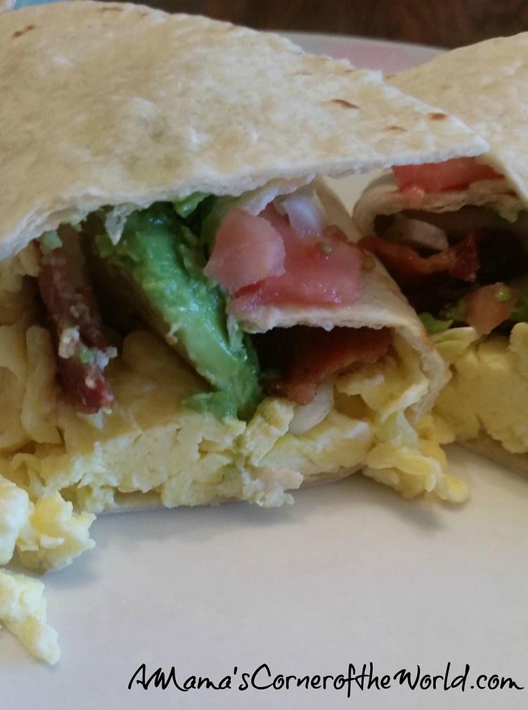 Tortilla wrap stuffed with bacon, avocado, tomato, scramled eggs
