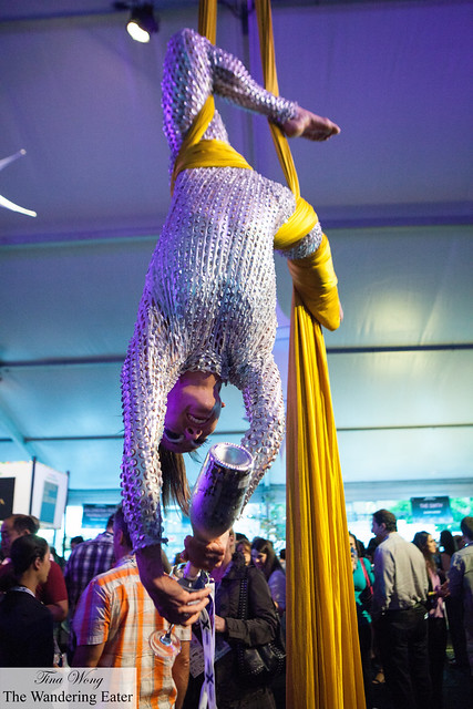 An aerial contortionist pouring Prosecco for guests