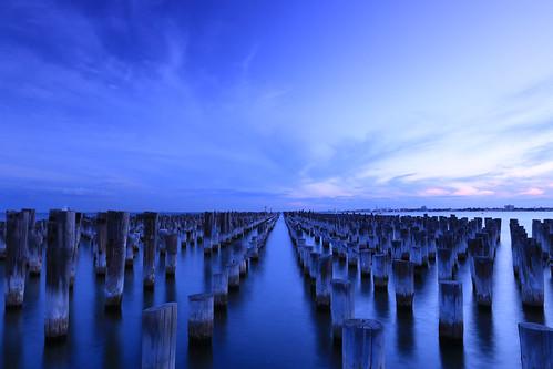 princespier portmelbourne melbourne victoria australia pilings posts wooden landscape waterscape coastal water bay portphillipbay evening sundown dusk sky clouds sea shoreline bluehour