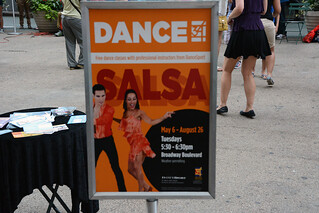 Picture Of Free Salsa Dancing Class Being Held In Herald Square At 34th Street Near Macy's Department Store In New York City. Salsa Dancing Tuesday's Between 5:30 - 6:30 PM From May 6 – August 26, 2014. Photo Taken Tuesday July 8, 2014