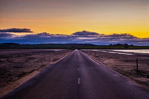 lindisfarne island causeway long straight road sand poles clouds cloud sunset