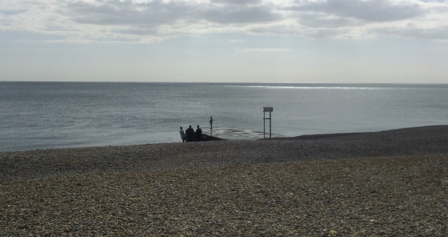 Lone fisherman... ...watched by tthree workmates on Brighton beach