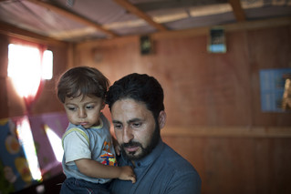 Ahmad holds his son Mouath in their makeshift home in the Ketermaya refugee camp | by World Bank Photo Collection