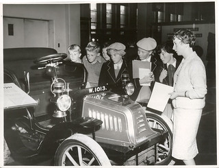 "Miss M.O. Conner (right) gives a talk on a 1902 ""Peugeot"" car which is on display at the Dominion Museum, Wellington."