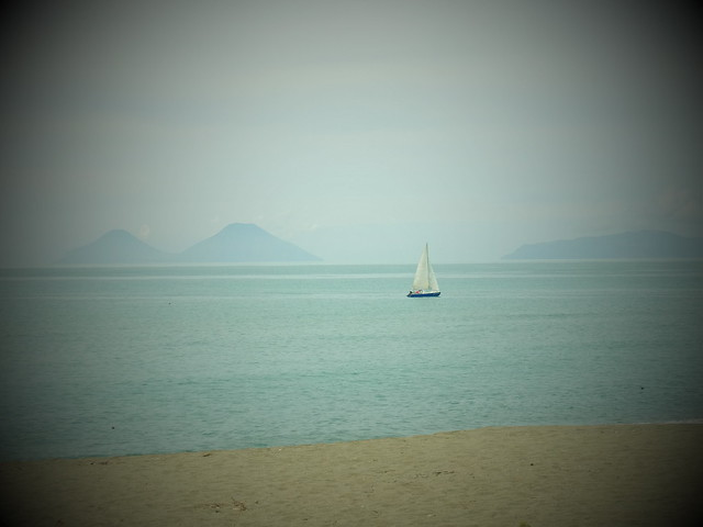 A solitary sailing with the Aeolian Islands in the background