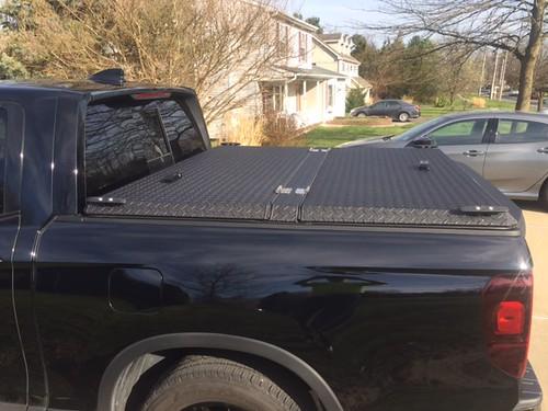 aluminum tonneaucover truckbedcover diamondback diamondplate pickuptruck blacktruck ruggedblack se honda ridgeline hr17 c driveway closed noaccessories cantedview driversideview 0015000001jgqj7aap